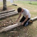 Using a drawknife to remove bark from the chestnut posts.